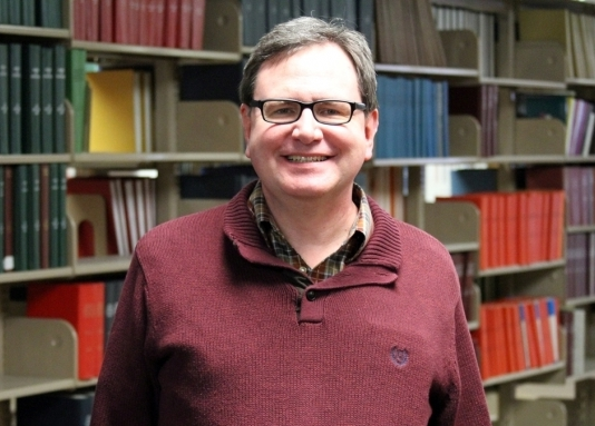 Image of Rob Cagna in front of a bakground of books on shelves.
