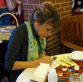 Photo of Cheryl Jacobson seated at a table doing caligraphy