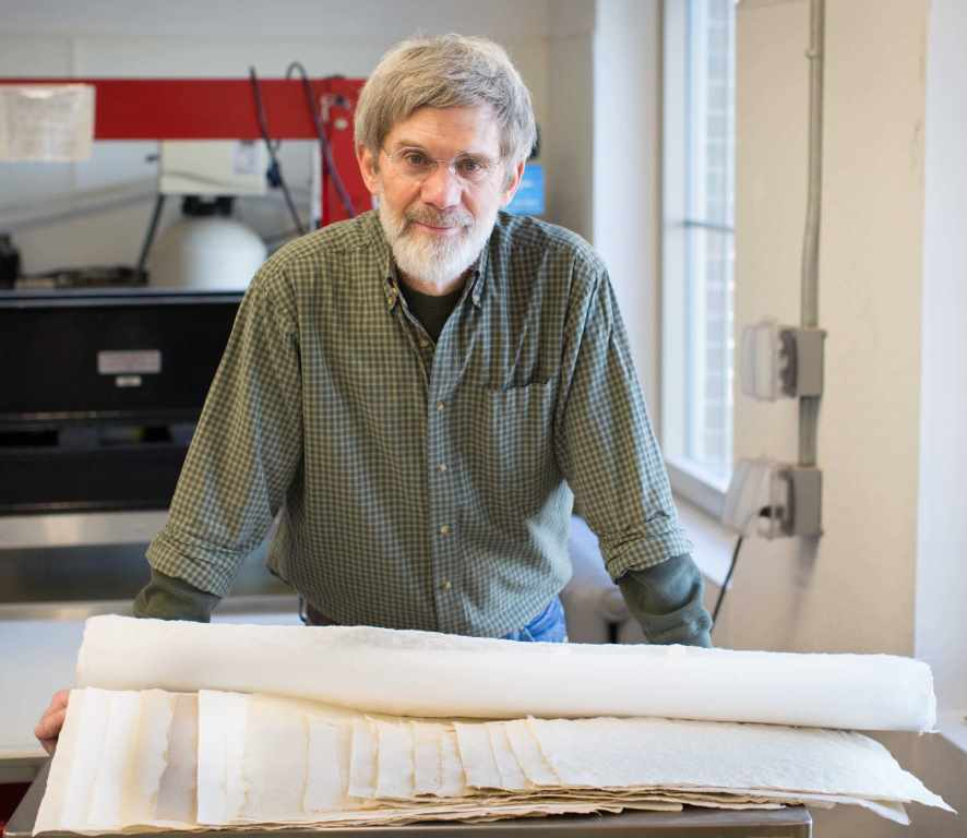 Image of Tim Barrett in paper studio, with several sheets of paper in the foreground.